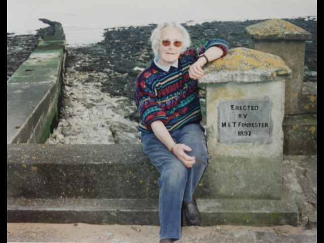 Ann Pickering after renovation of the plaque commemorating the building of the sea wall at Port Soderick, 2000.