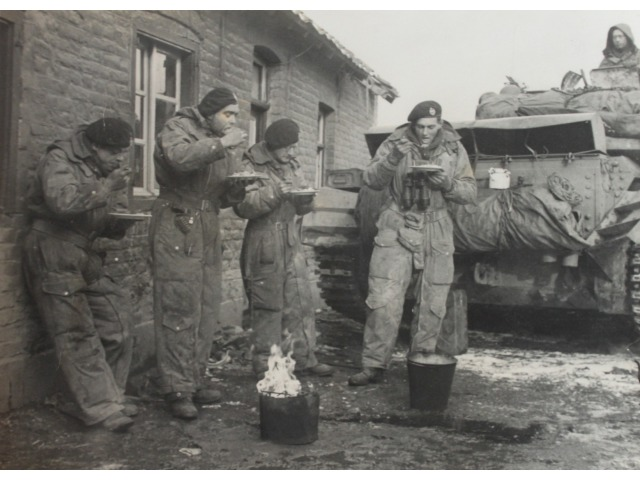 An image from Mr Hector Duff's personal collection, showing soldiers during WWII eating a meal during the advance through Europe following D-Day.