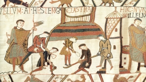 A scene from the Bayeux Tapestry showing the Normans building a castle. Note how the different coloured stiching indicates layers of different materials being used in the construction.